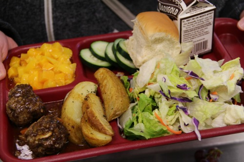 School lunch with vegetables, meat, potatoes, and milk