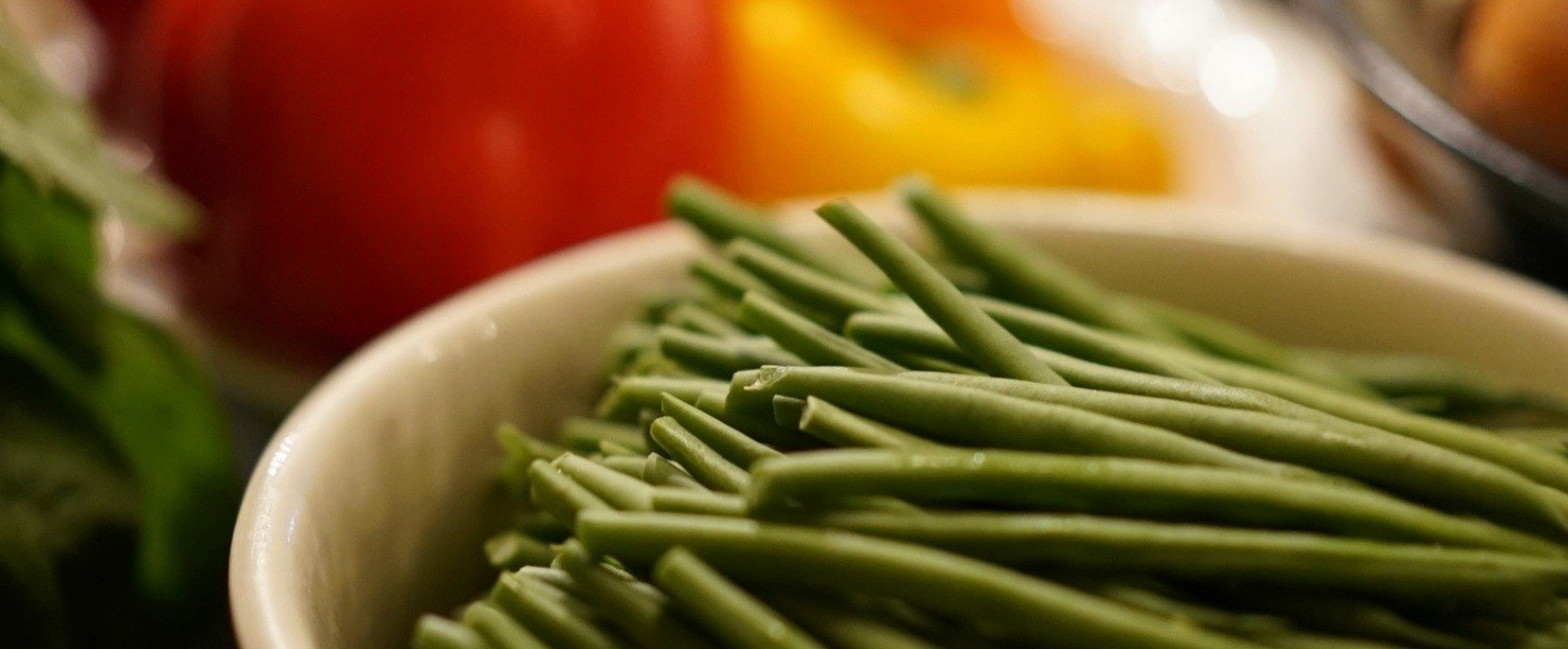 Bowl of green beans in front of bell peppers
