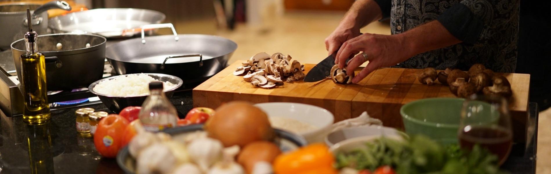 Chef chopping mushrooms on a cutting board