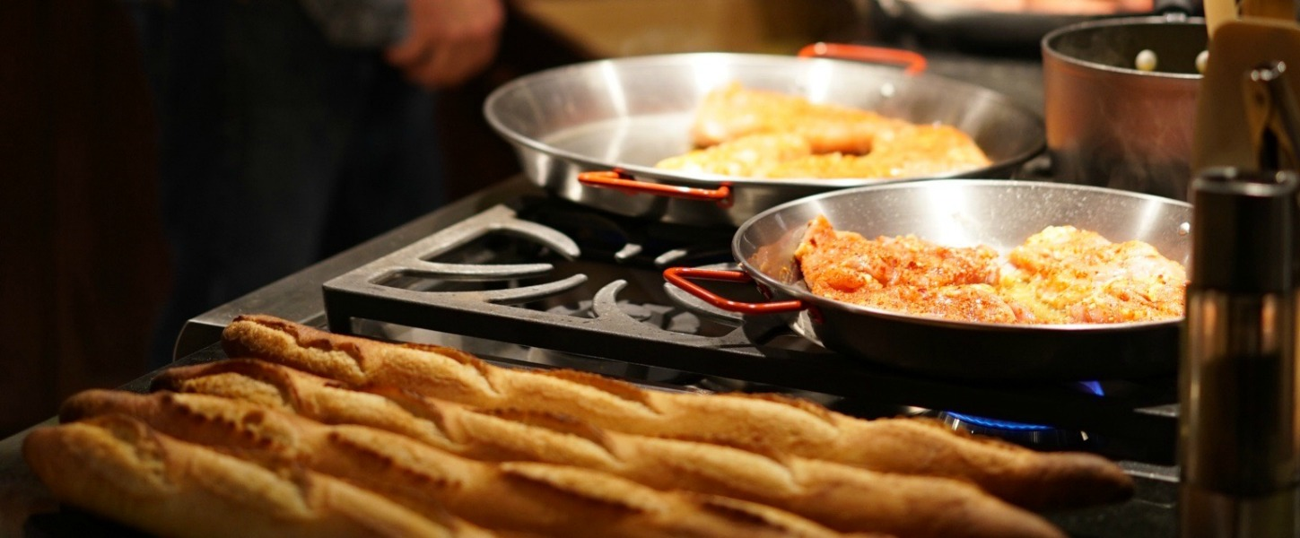 Pans of food cooking on stove and french bread on counter